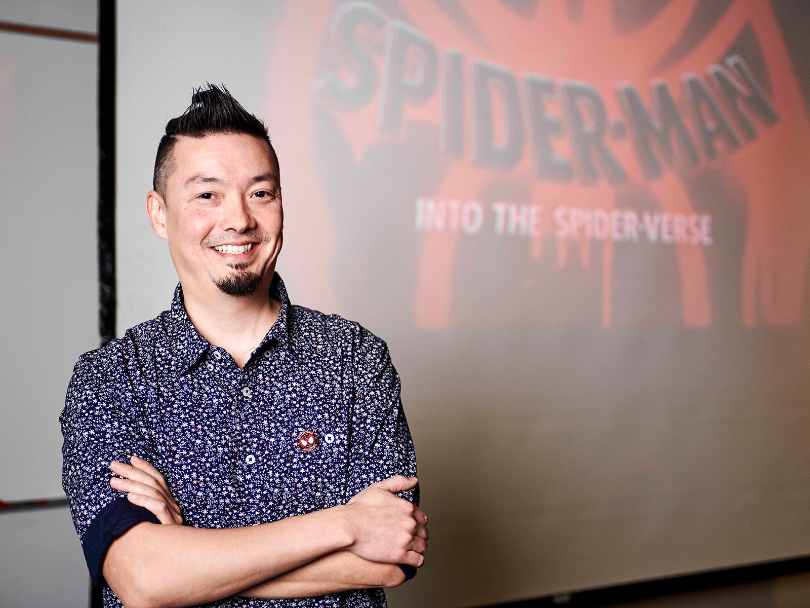 Nick Kondo smiles in front of a projection of Spider-Man: Into the Spider-Verse's title card.