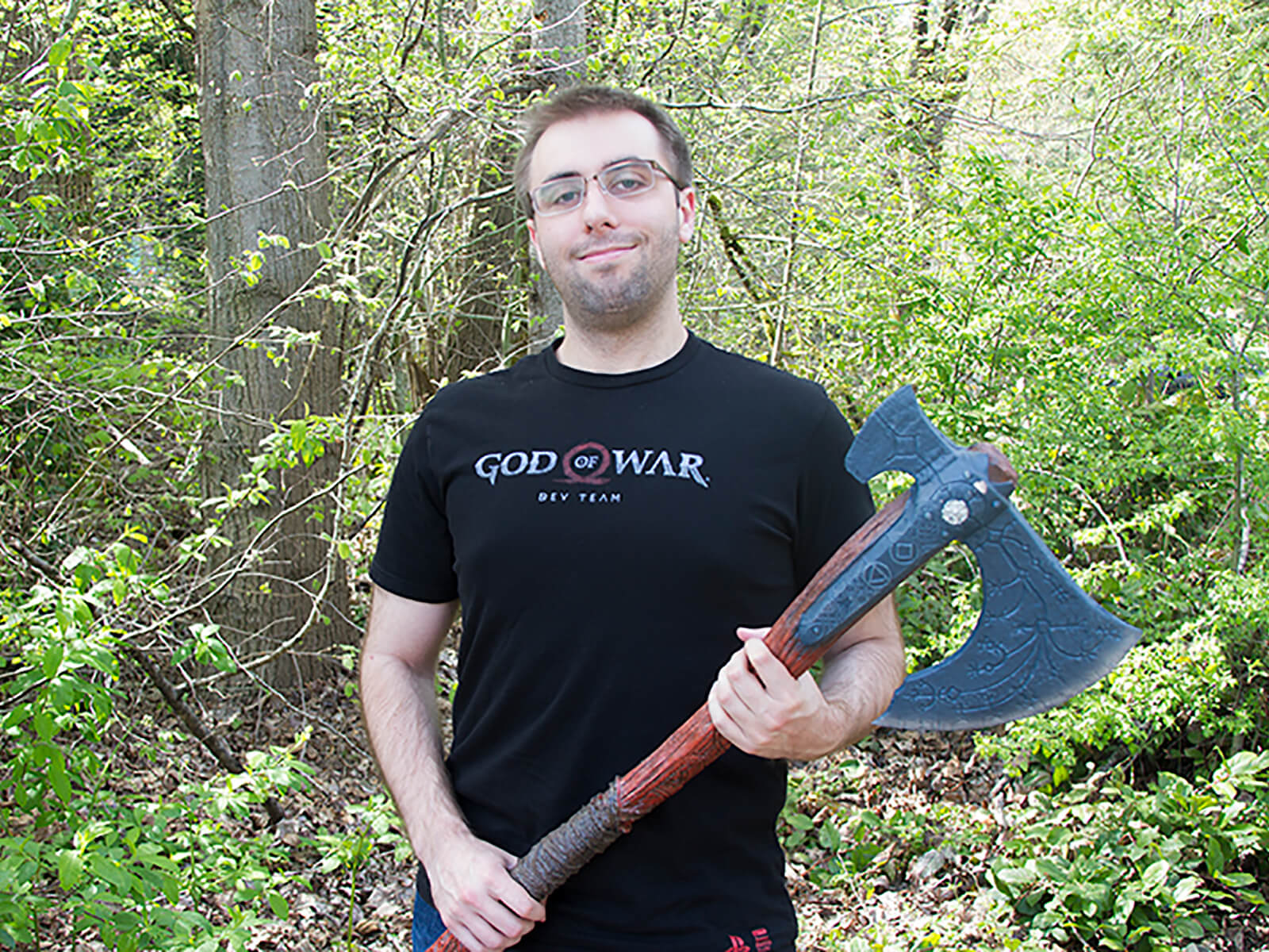 DigiPen alumni Ryan Baker poses with a fake ax on the DigiPen campus