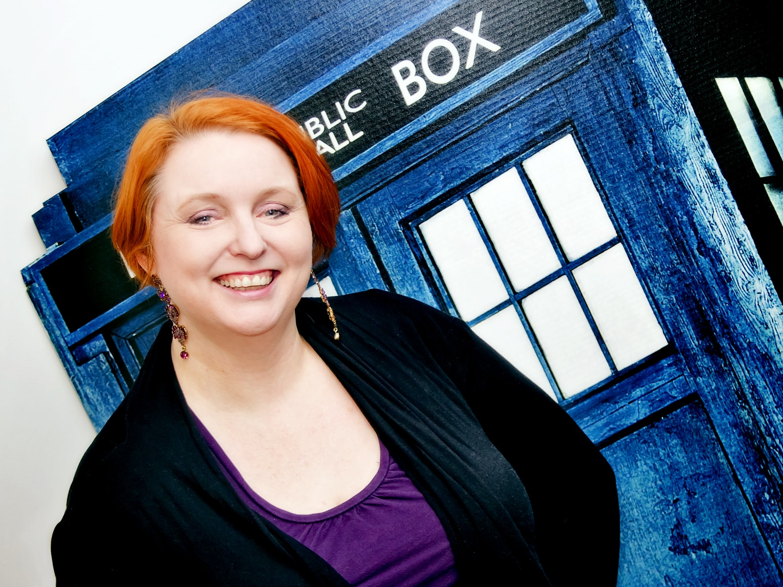 DigiPen lecturer Sonia Michaels smiling in front of the Dr. Who Tardis (a blue police box time machine) cutout in her office