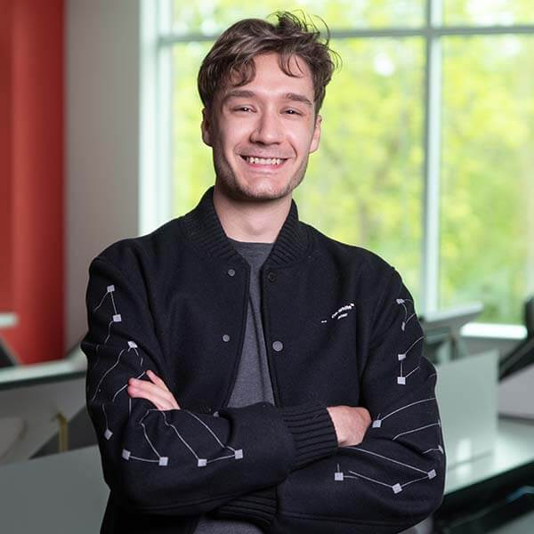 Christophe Bouchard in lecture hall standing with arms crossed wearing a black jacket