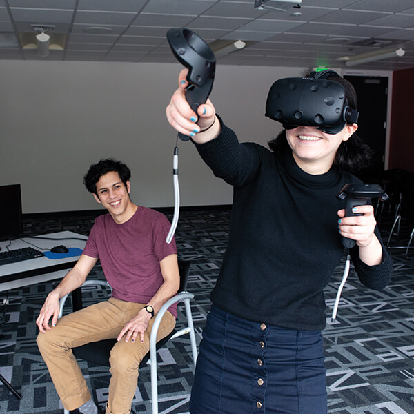 A DigiPen student tries out their VR game team project as their teammates smile at them.