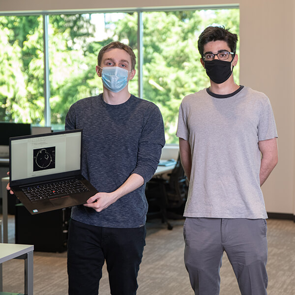 DigiPen BS in Computer Science in Machine Learning sophomores Eric Zander and Andrew Ardeleanu pose in a campus computer lab wearing face masks.