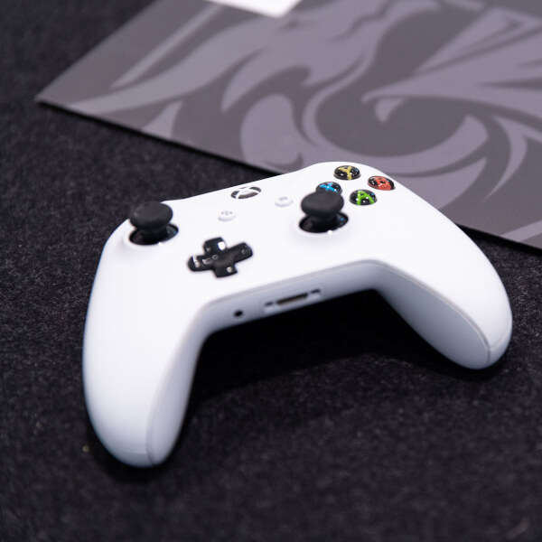 White Xbox controller next to grey DigiPen folder