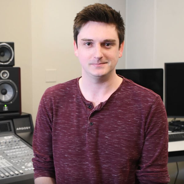 DigiPen graduate Max Hayes smiles in the campus audio lab.