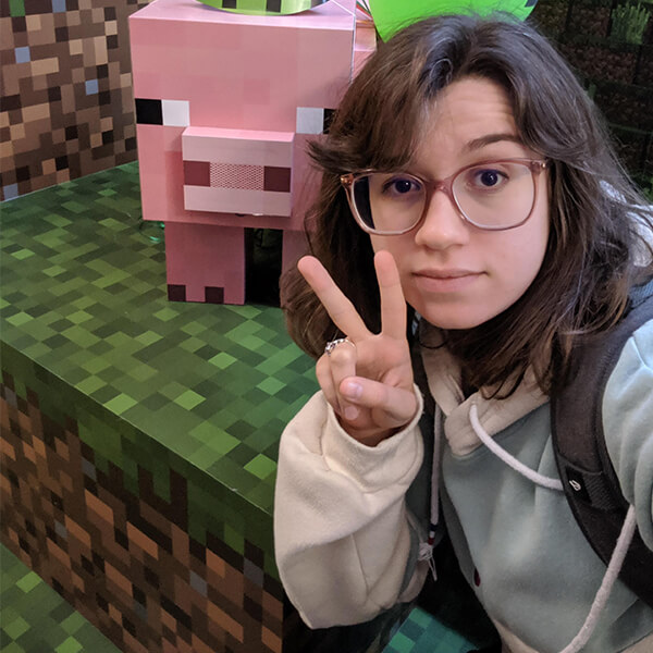 DigiPen graduate and Mojang artist Kelly Greene flashes a peace sign next to Minecraft Earth's Muddy Pig