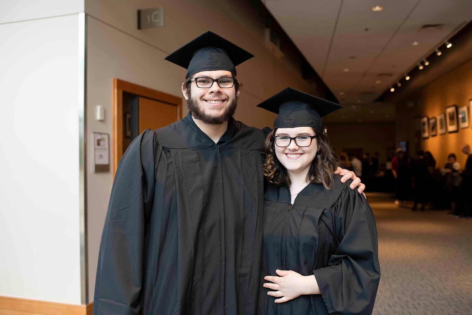 A man and woman in graduation robes and mortarboards pose for a photo in a convention center hallway.
