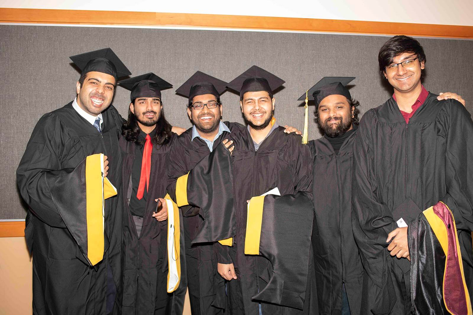 A group of master's degree students pose in graduate robes and mortarboards holding their colored candidate hoods.