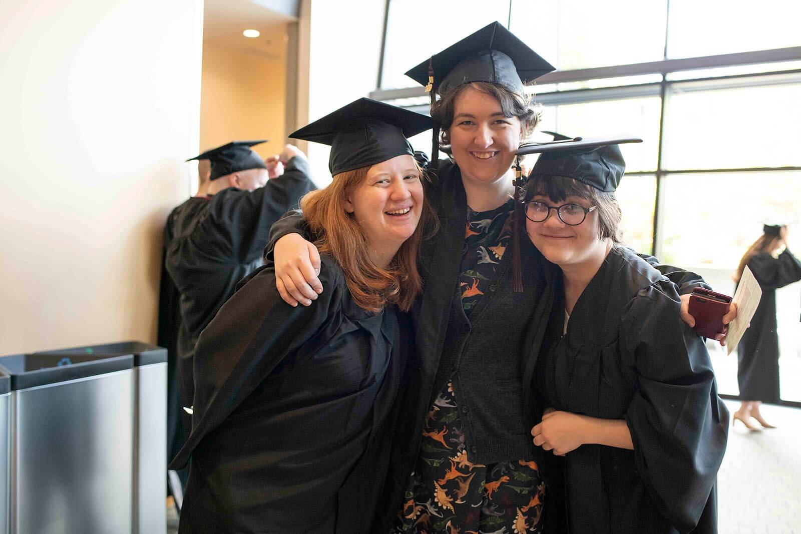 Three students in graduation robes and mortarboards embrace each other for a photo in a convention center hallway.