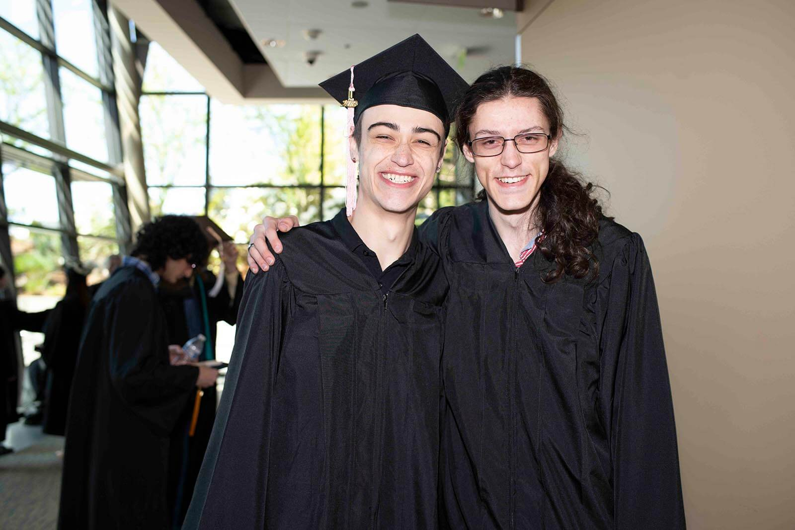 Two students in graduation garb smile for a photo in a convention center hallway.