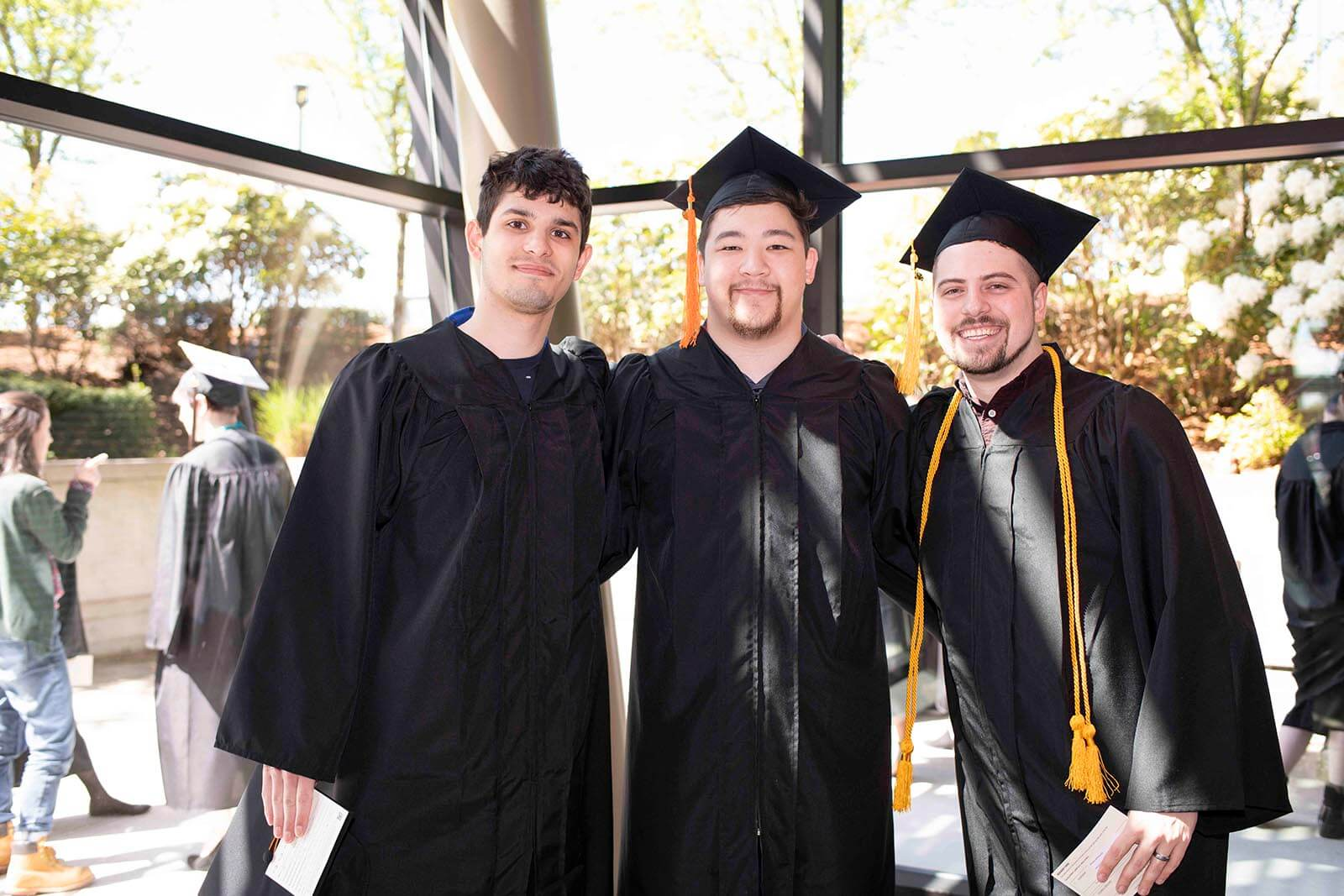 Three students in graduation robes and mortarboards pose for a photo in front of a floor-to-ceiling glass wall.