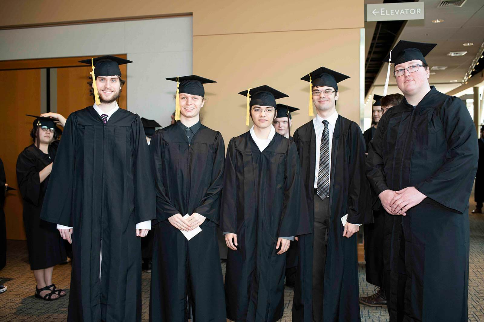 A group of graduating students pose in black robes and mortarboards in a hallway.