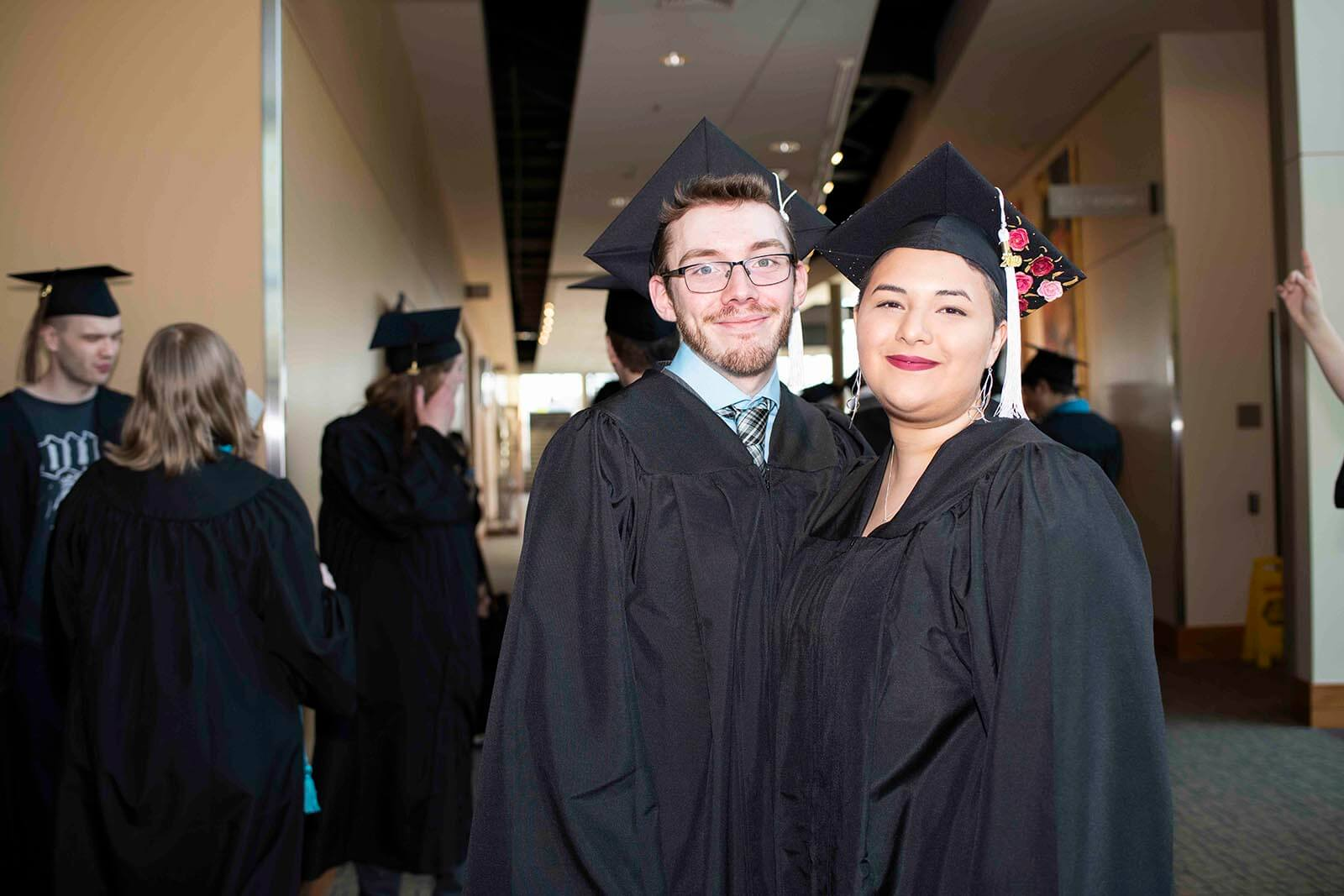 Two students in black graduation garb pose for a photo in a convention center hallway.