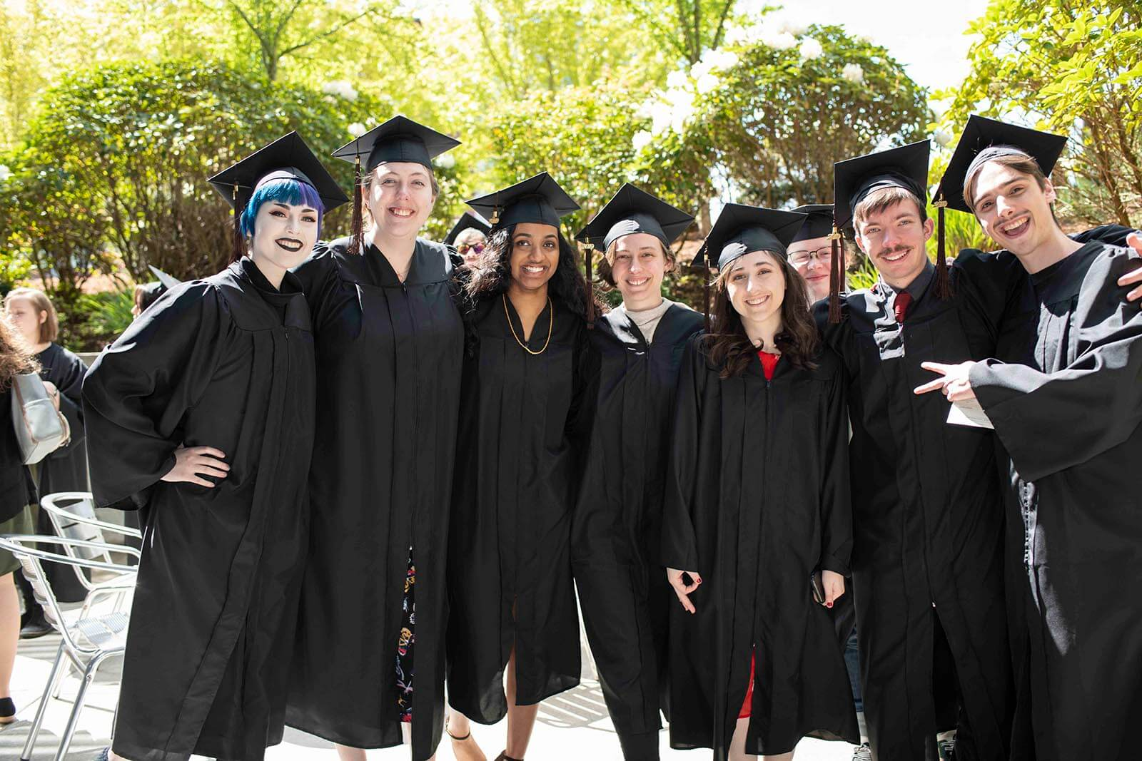 A group of students in graduation robes and mortarboards pose for a photo in a tree-lined courtyard.