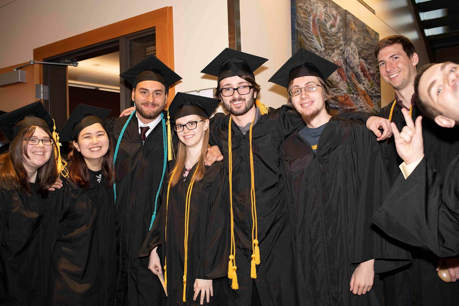 A group of graduating students in robes and mortarboards pose for a photo in a convention center hallway.