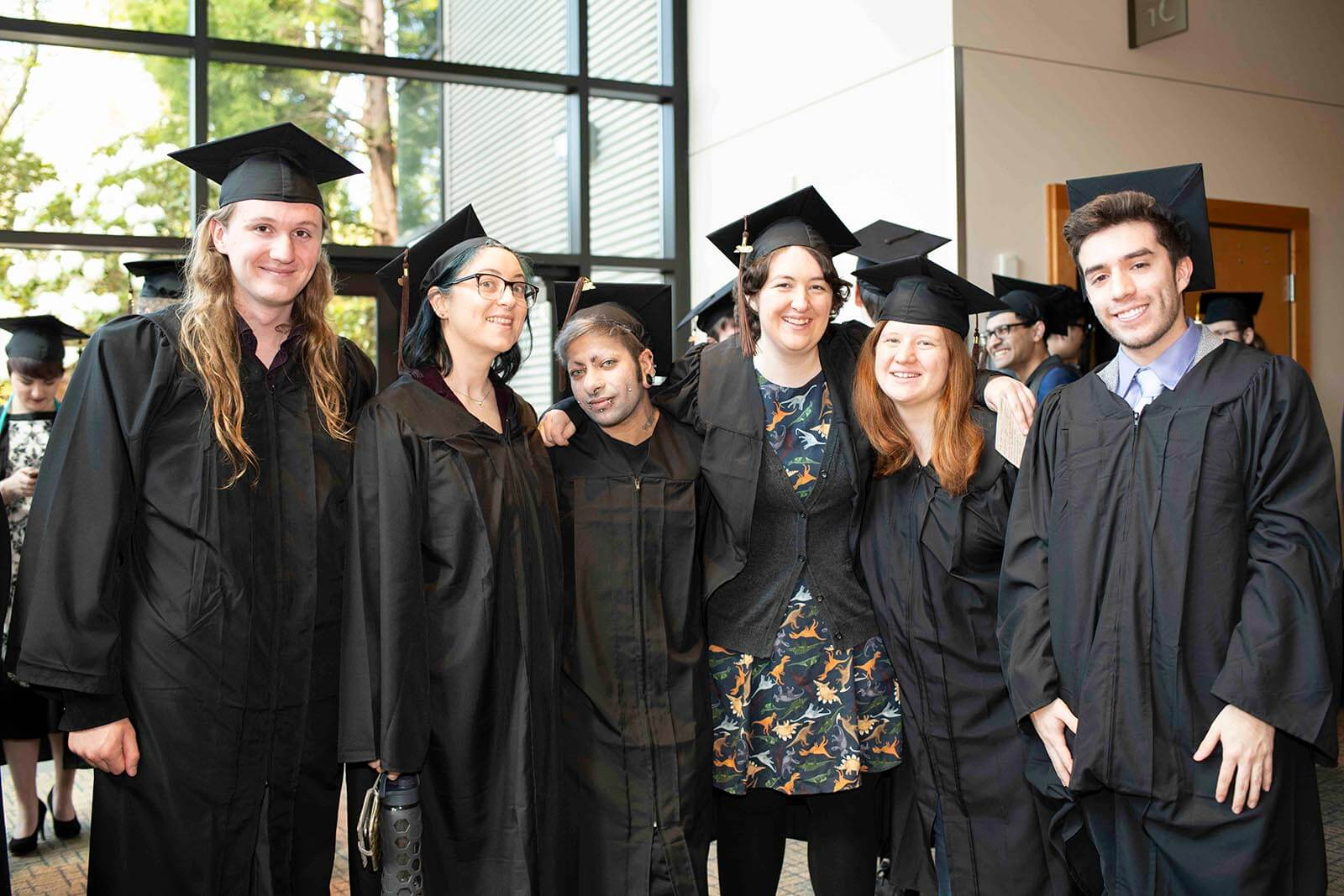 A group of graduating students in robes and mortarboards pose for a photo in a lobby area.