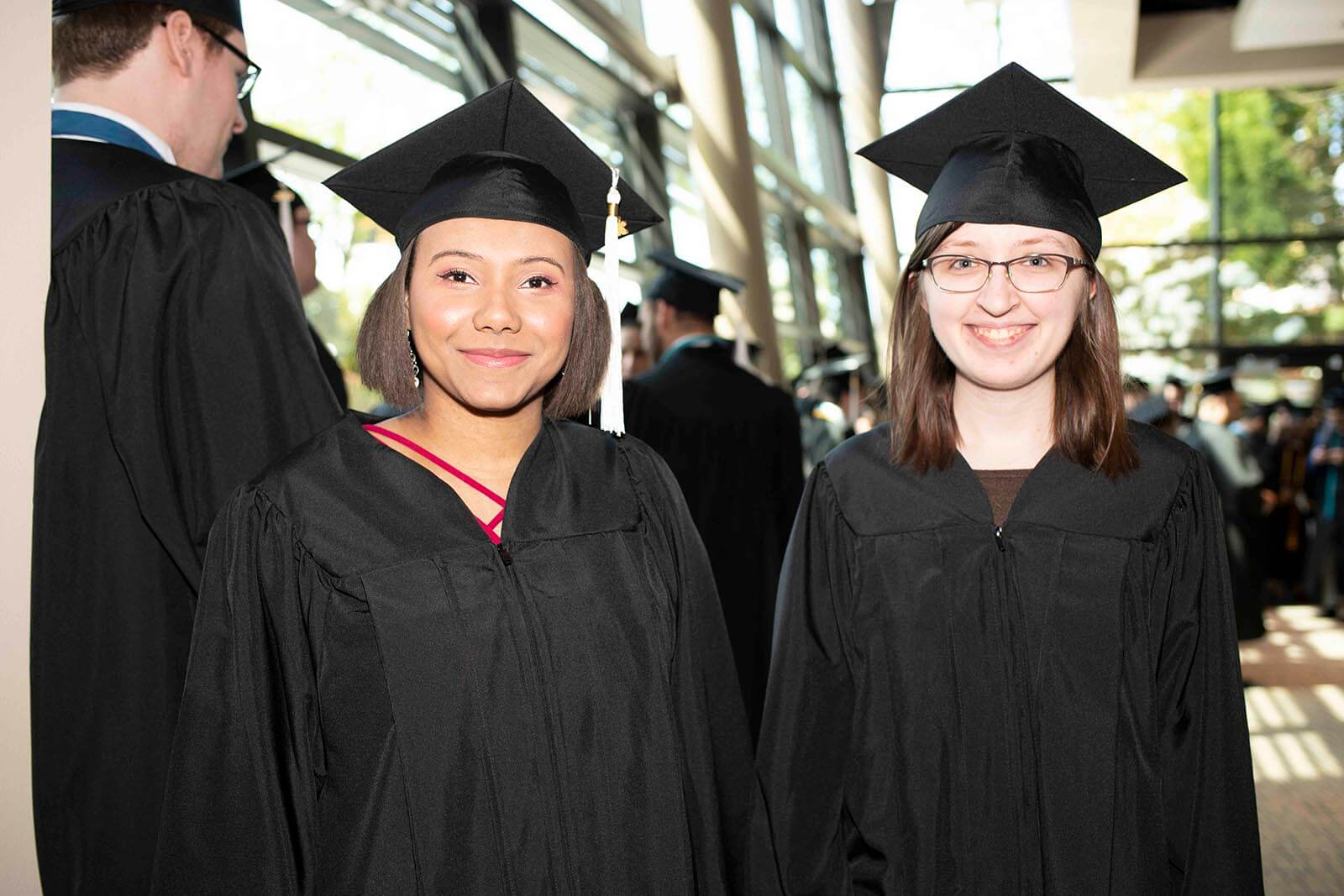 Two students in graduate garb smile for a photo in a convention center lobby area.