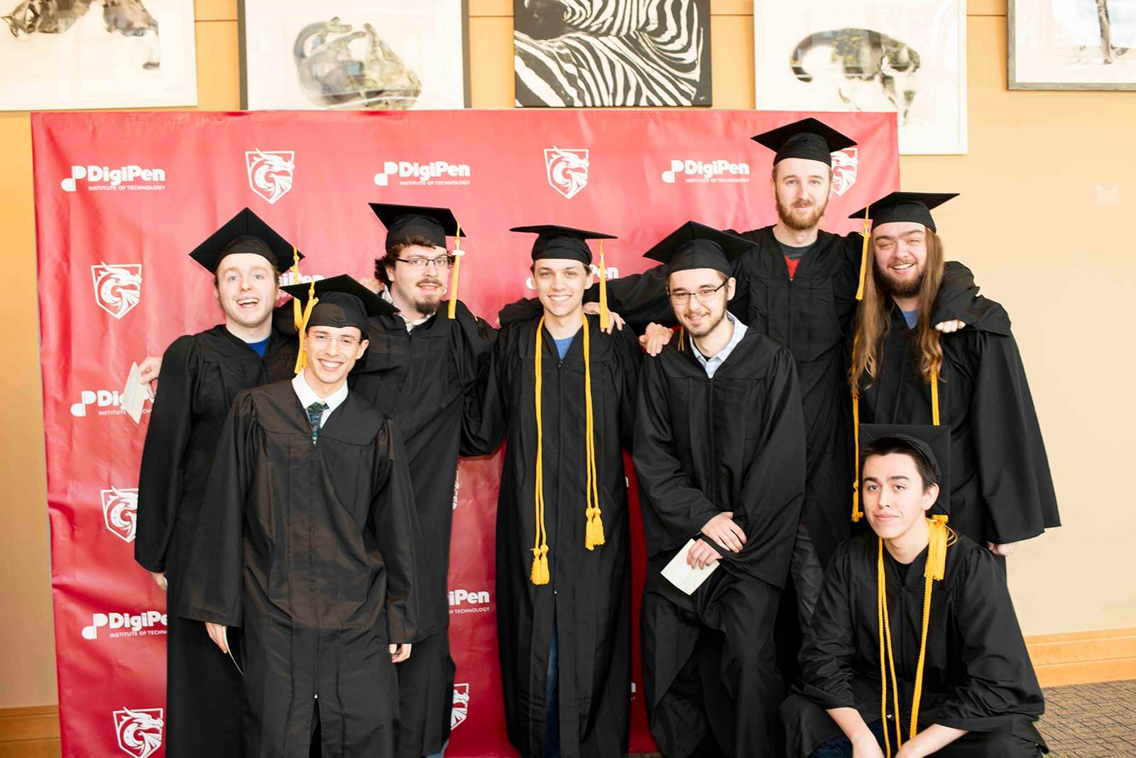A group of students in graduation garb pose in front of a red backdrop bearing DigiPen's logo and name.