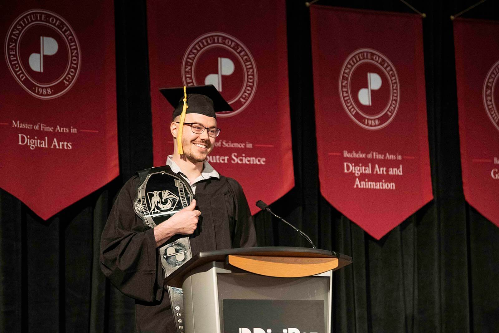 Benjamin Albertson-Gass stands at a podium in graduate garb holding a wrestling-style belt bearing the DigiPen logo.