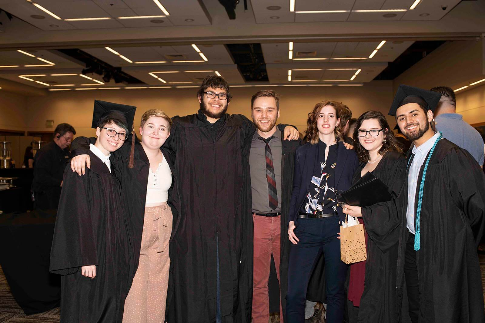 Newly graduated students in black robes pose together in a convention center meeting room.