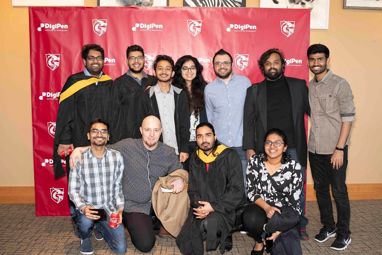 A group of people, some in graduation robes pose in front of a red backdrop bearing DigiPen's logo and name.