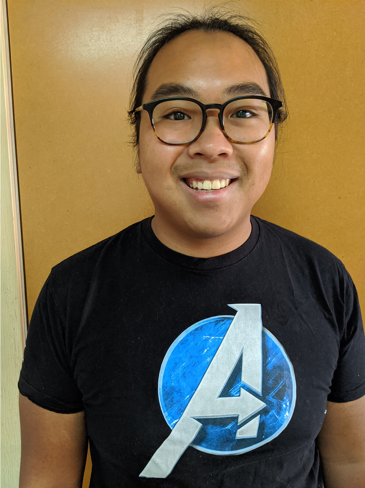 DigiPen graduate Kevin Do poses in an Avengers t-shirt
