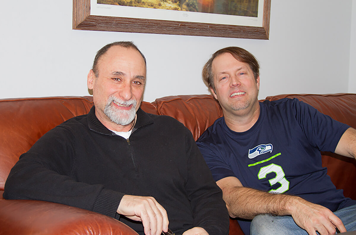 Former Disney animators and current DigiPen professors Anthony De Fato and Richard Morgan smiling on a couch