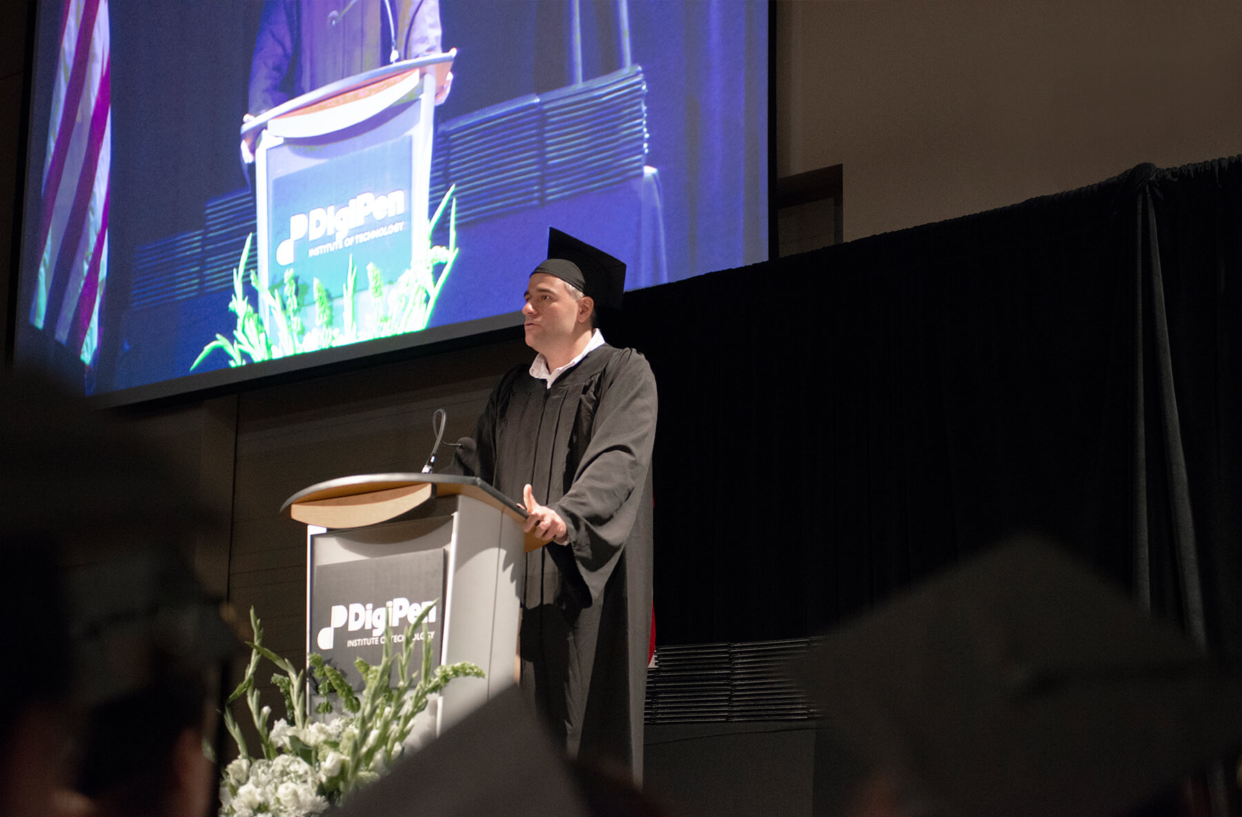 Anthony Saulls delivers a speech on stage at the 2018 DigiPen commencement ceremony.