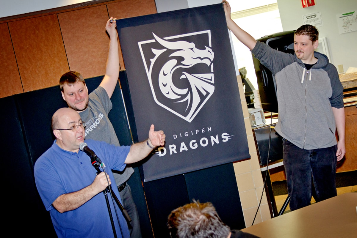 DigiPen founder and president Claude Comair unveiling the DigiPen dragon mascot during a ceremony in the DigiPen cafe