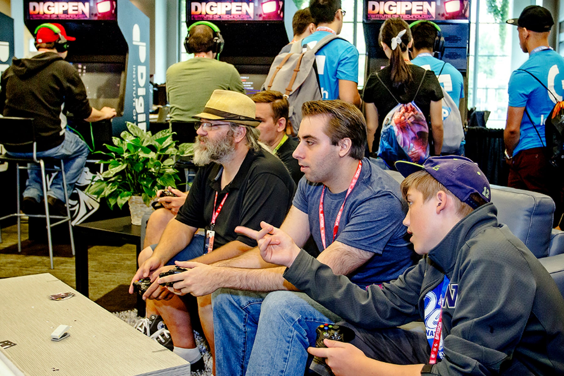 PAX attendees play games on a couch in the DigiPen arcade booth
