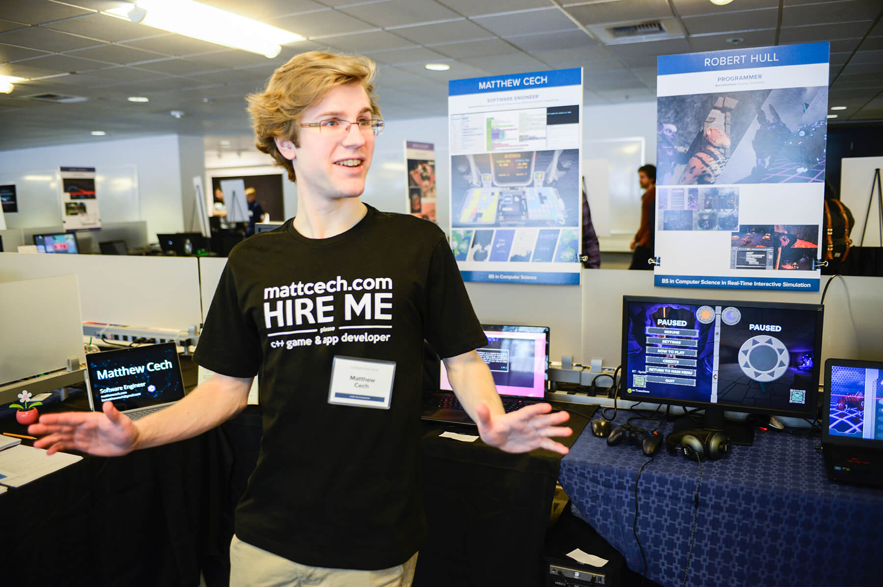 "DigiPen student Matt Cech wearing a t-shirt that says ""Hire Me"" and gives his website address"