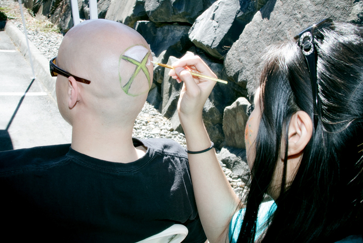 A DigiPen attendee getting his bald head painted with the Microsoft Xbox logo