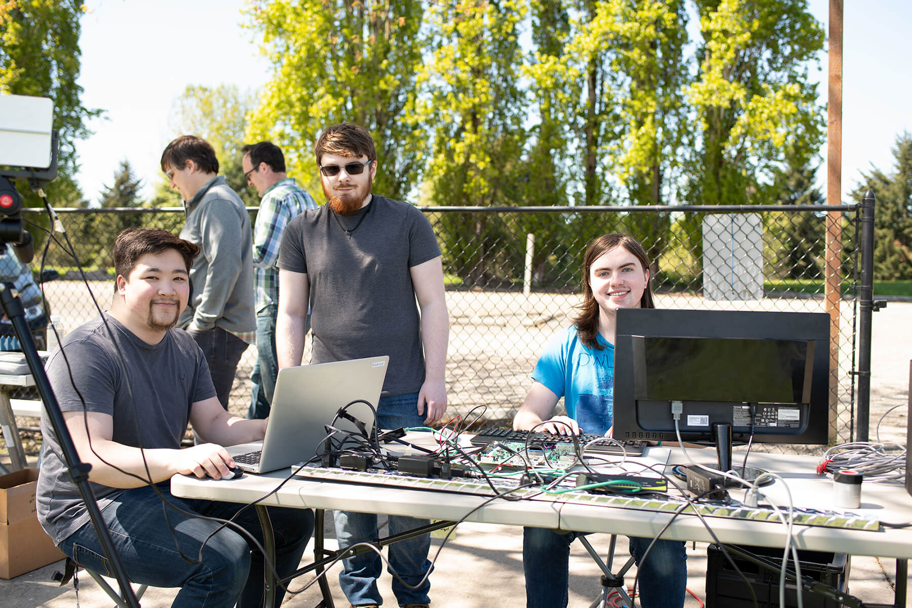 Three students pose in a park behind a computer setup that includes a laptop, monitor, radar system, and wires.
