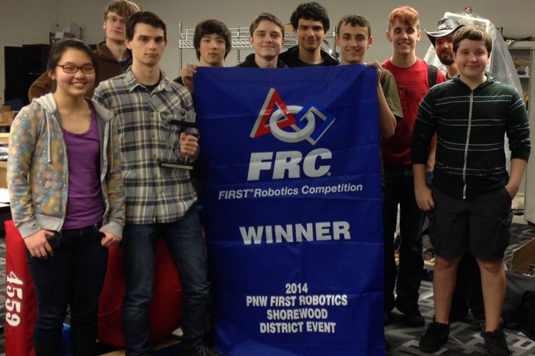 Nine students and one coach of first draft standing around Shorewood District Championship banner