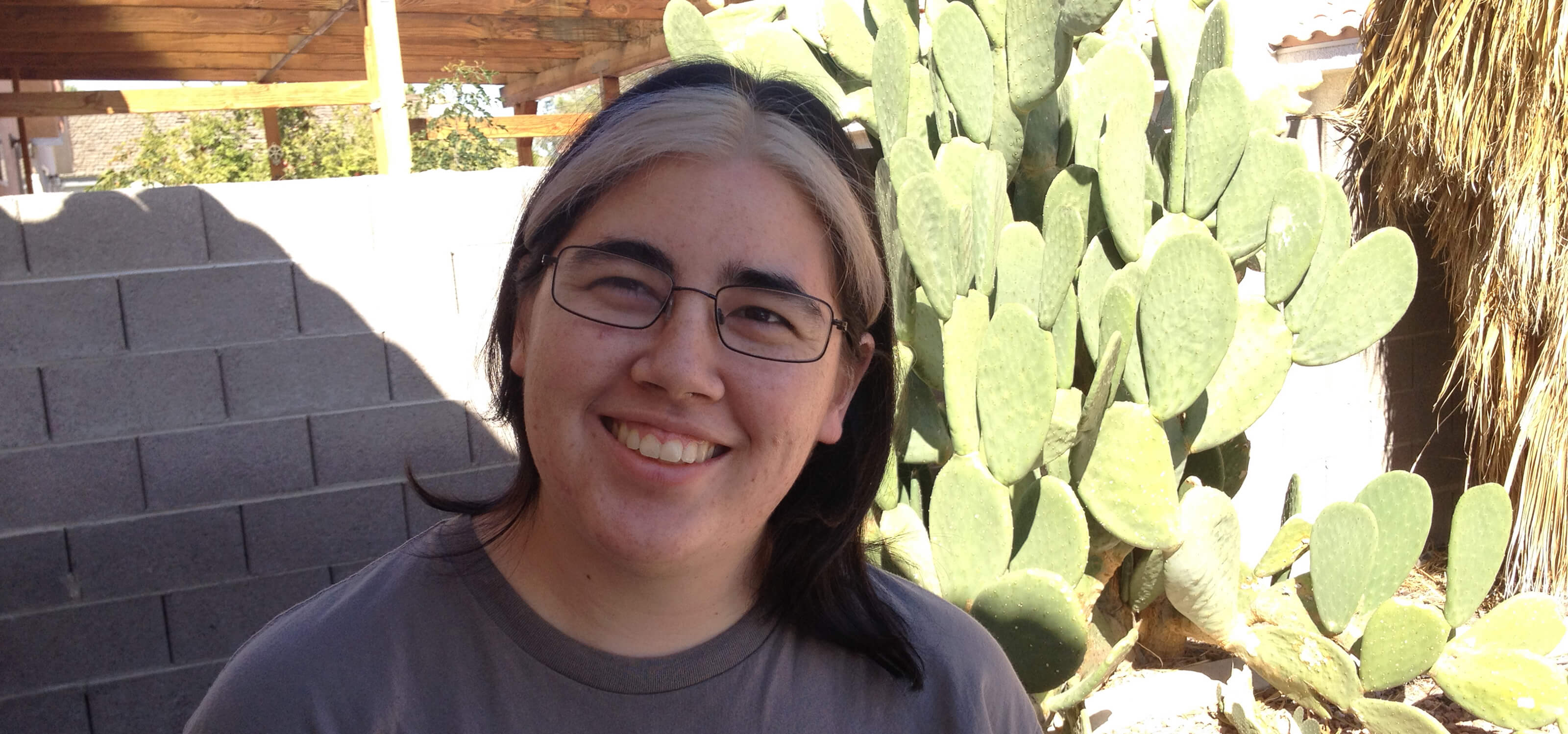 DigiPen graduate and Spry Fox senior software engineer Molly Jameson poses in front of a cactus.