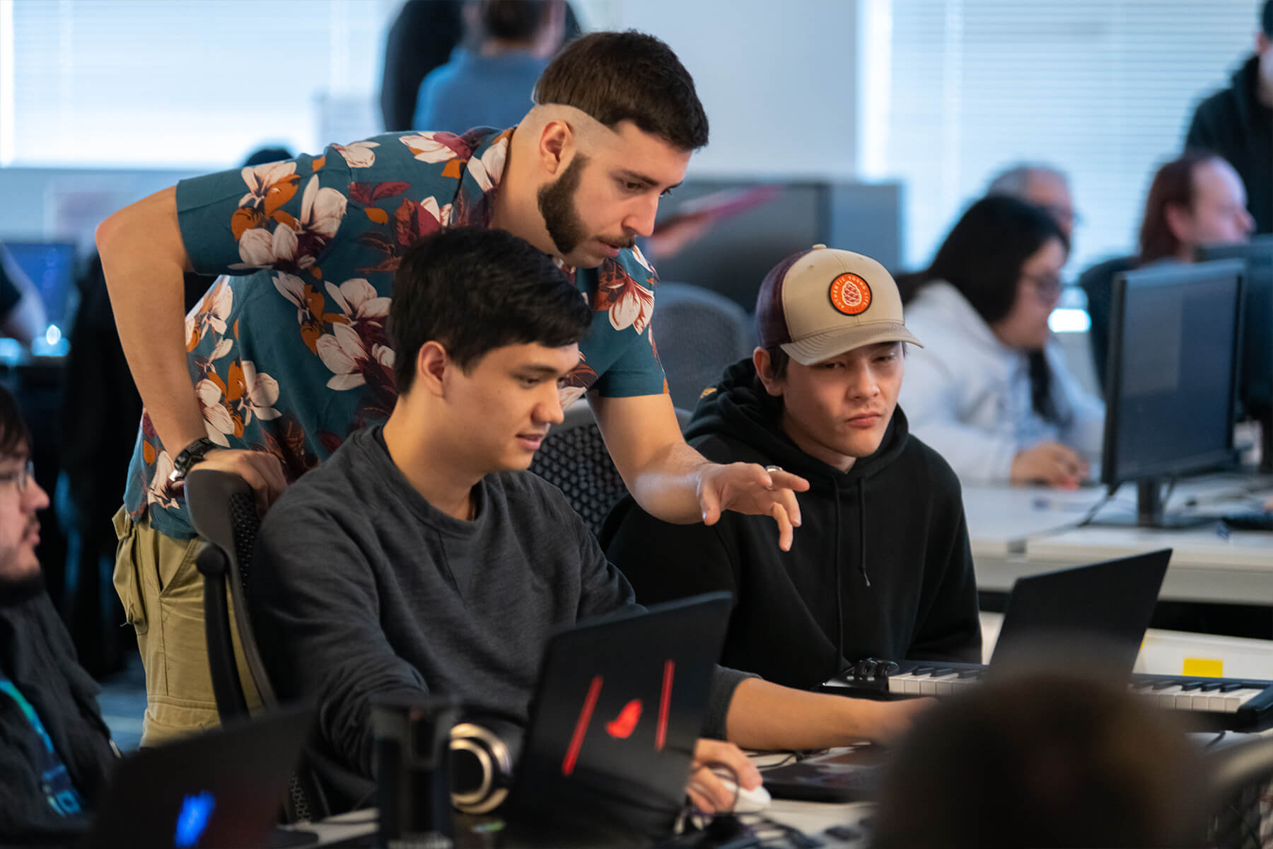 A student in a Hawaiian shirt gestures towards his teammate's computer screen as another team member looks on.
