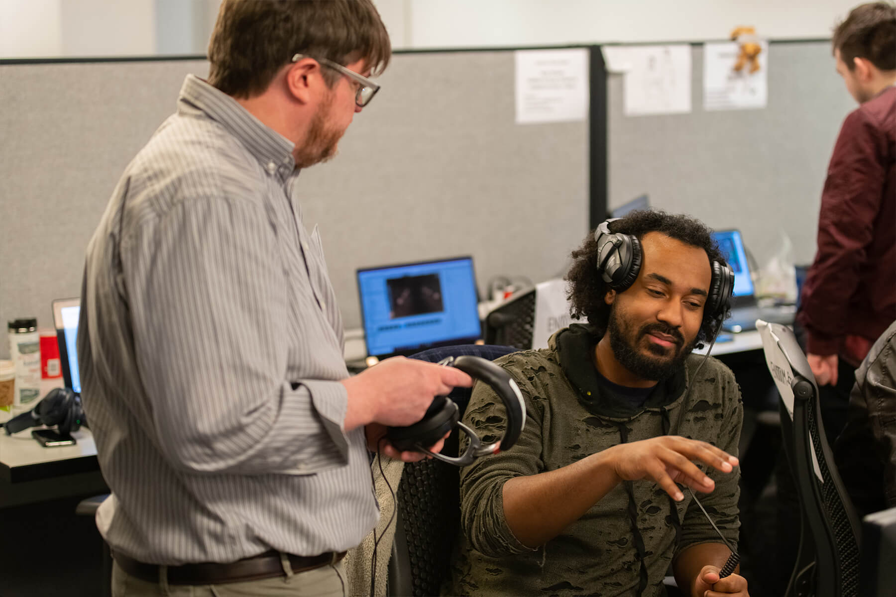 A professor takes his headphones off to chat with a student, also wearing headphones, about their work.