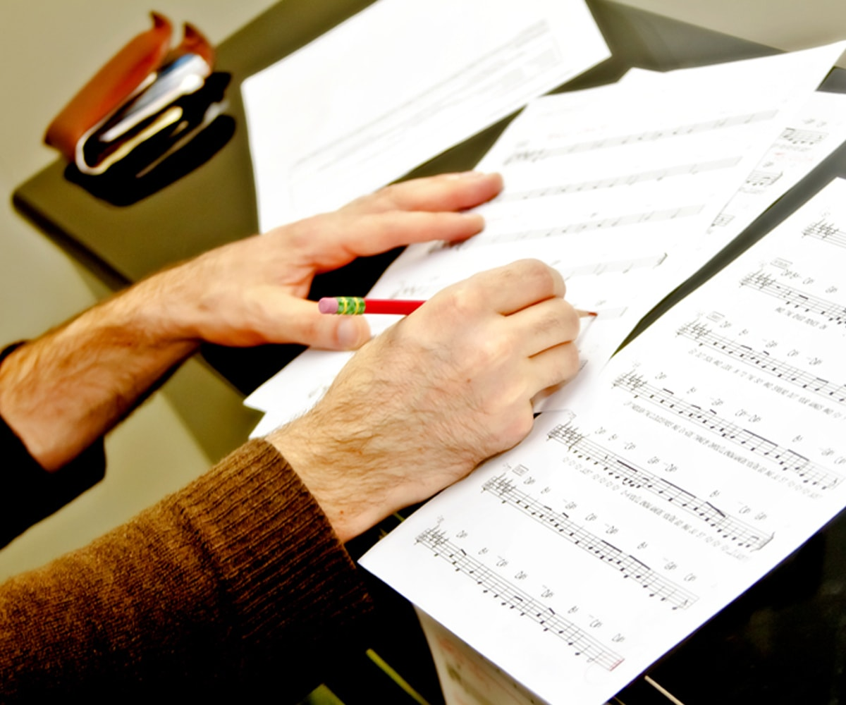 DigiPen student marking sheet music with a red pencil