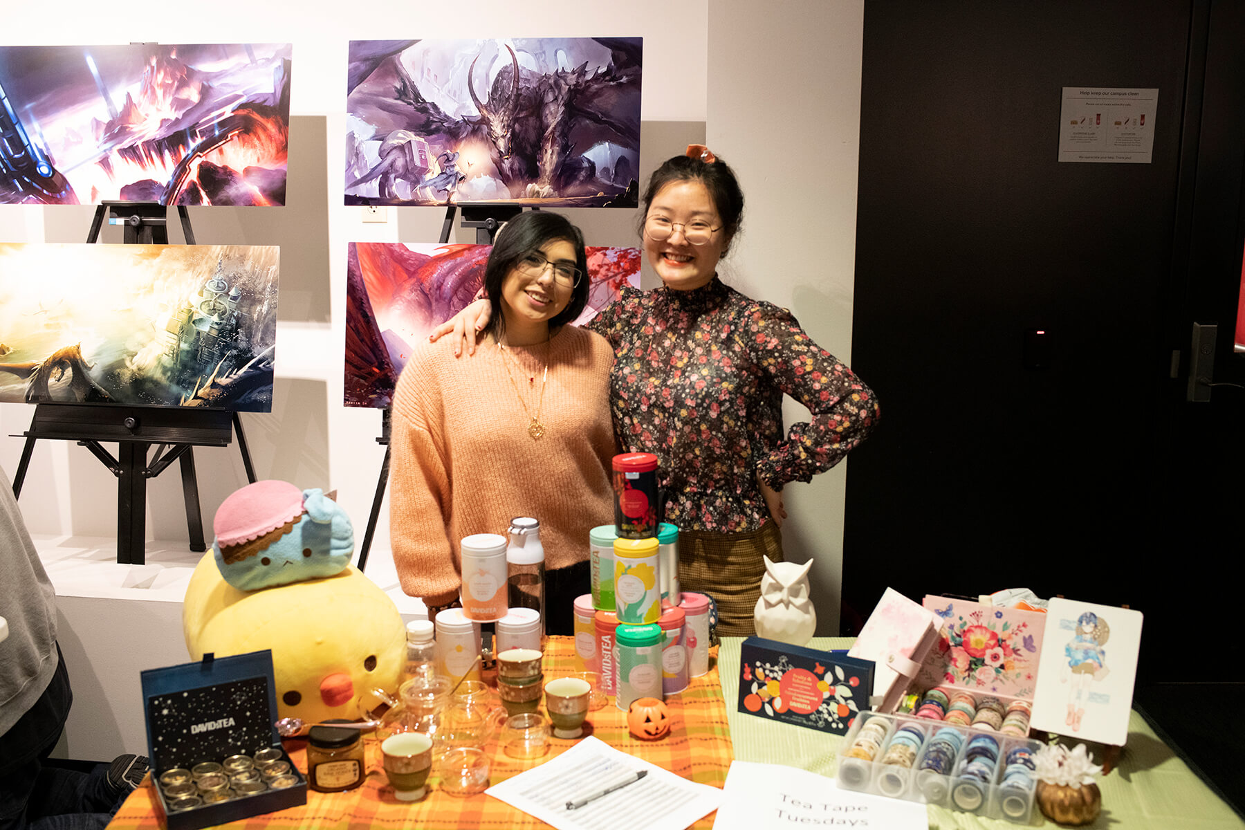 Two students stand behind a table arranged with teas and knickknacks.