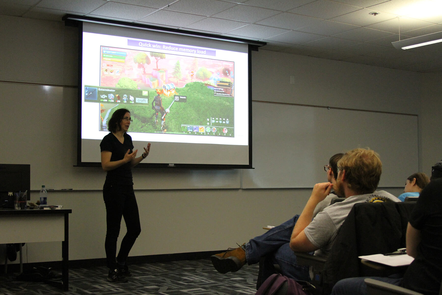 Dr. Hodent gestures towards students during her lecture, with scenes from a Fortnite play test projected behind her.