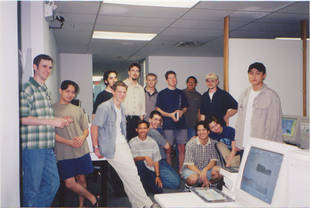 Duncan Shields poses with 13 fellow students in a computer lab at DigiPen Vancouver.
