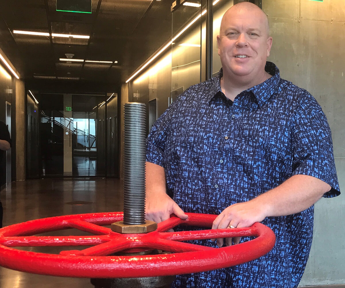 Eric Smith poses with the actual valve at the Valve office