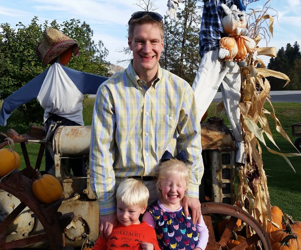 Erik Mohrmann and his two kids smiling at a pumpkin patch