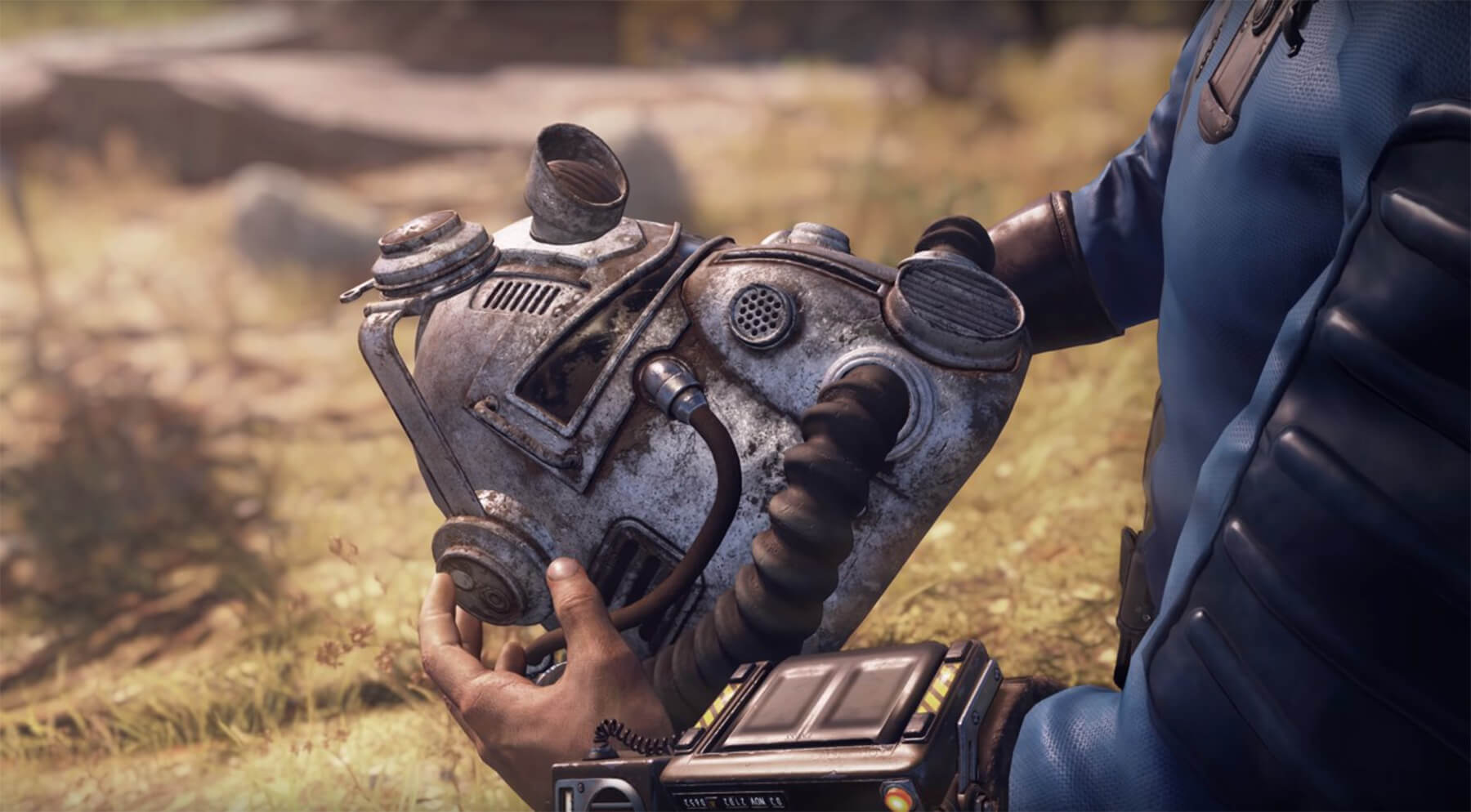 A Fallout 76 character holds a nuclear radiation helmet.