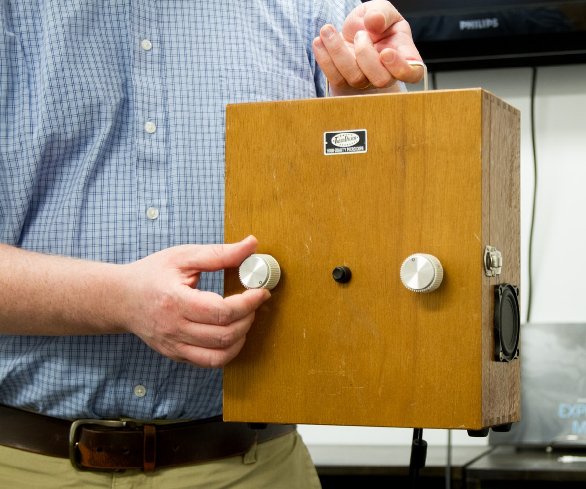 Greg Dixon shows off his Space Regenerator, a small wooden box with two knobs on the front and a speaker on the side