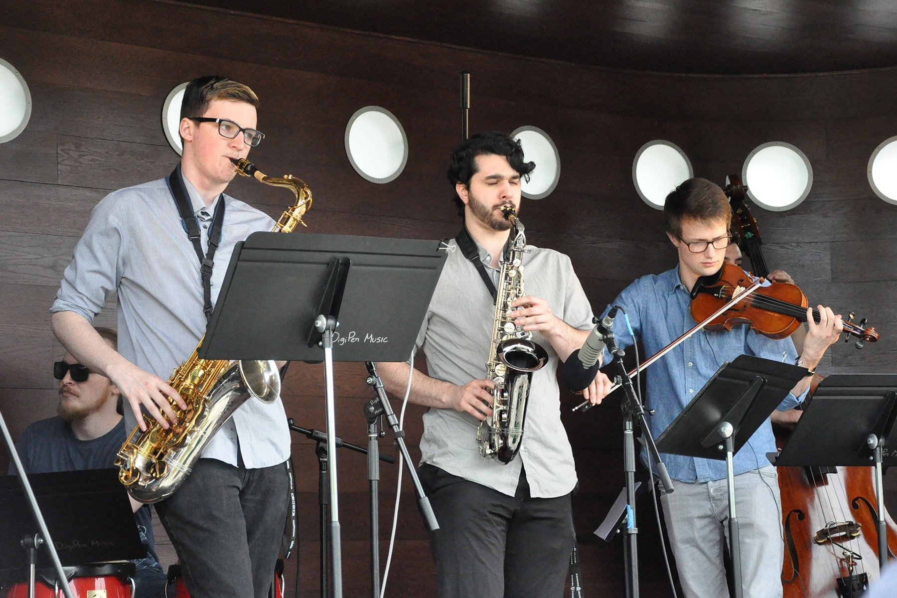 DigiPen Jazz Ensemble members playing saxophones, drums and violin on a portable stage