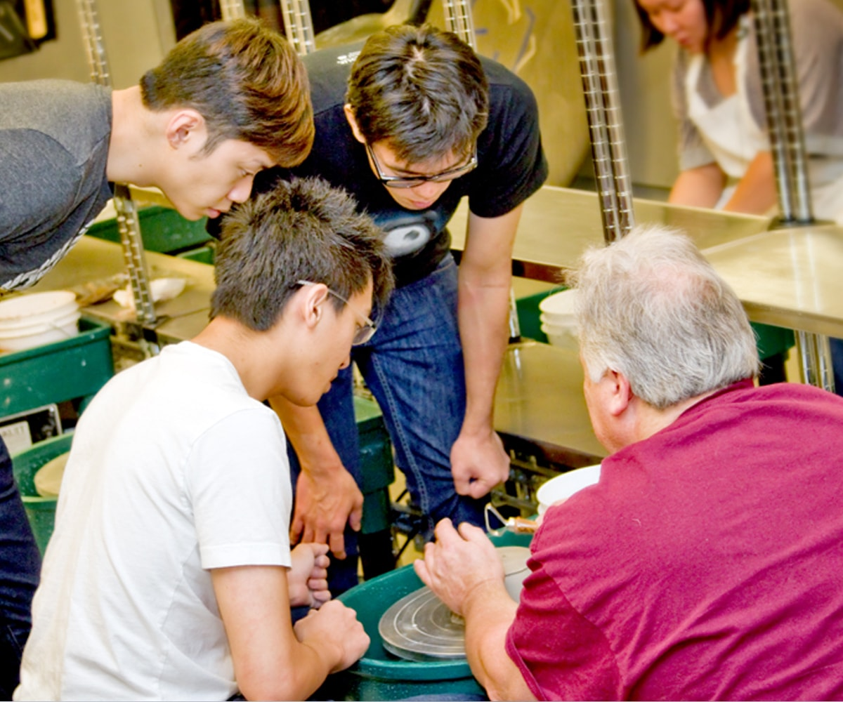 Ken Turner instructs a group of DigiPen students on a ceramics wheel
