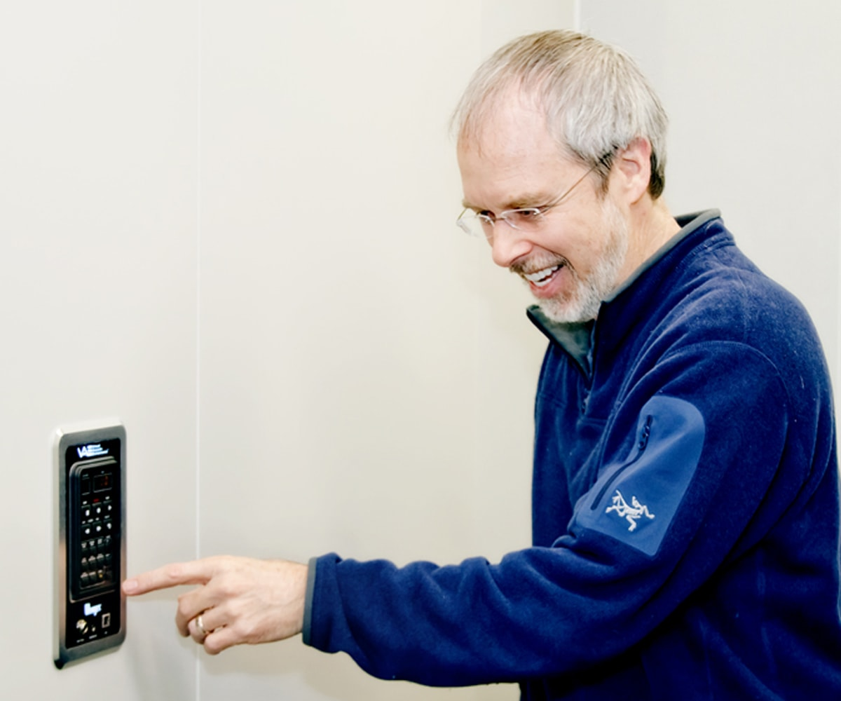 Lawrence Schwedler pointing to a wall-mounted control box in a new DigiPen sound lab practice room