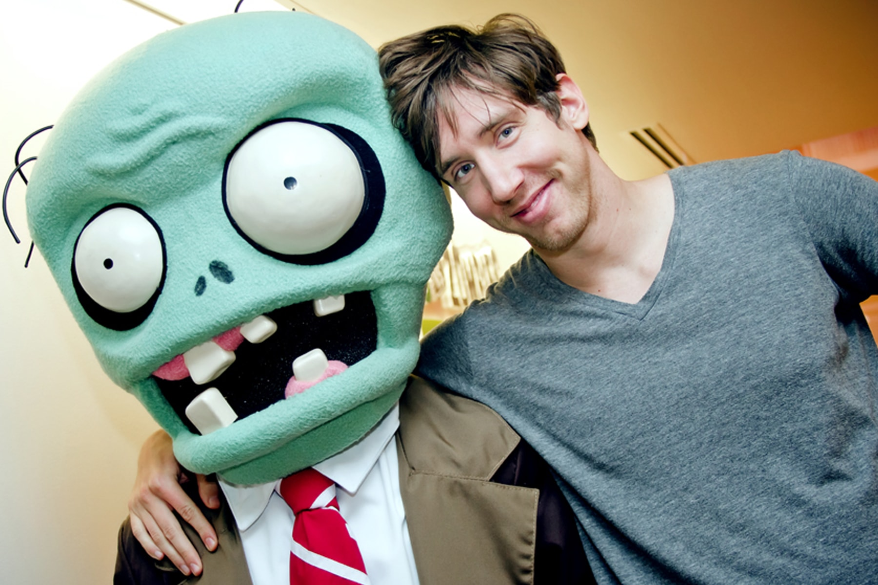 Mark Barrett smiling with his arm around the PopCap zombie mascot