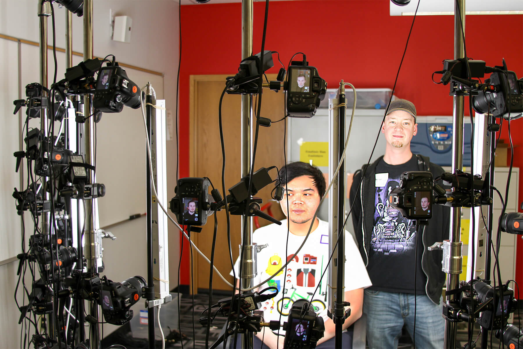 Matt Heiniger poses with a student behind his mobile 40-camera photogrammetry rig.