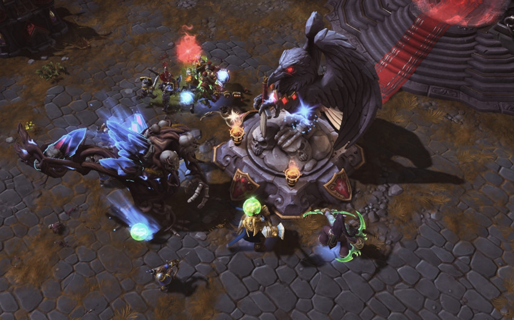 Top-down view of action happening beside a statue of a bird in Heroes of the Storm